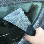Eine Person enteist mit einem Eiskratzer die Seitenscheibe ihres Autos